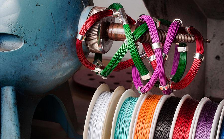 Pulseras modelo doble con diferentes motivos en plata e hilos de acero de colores